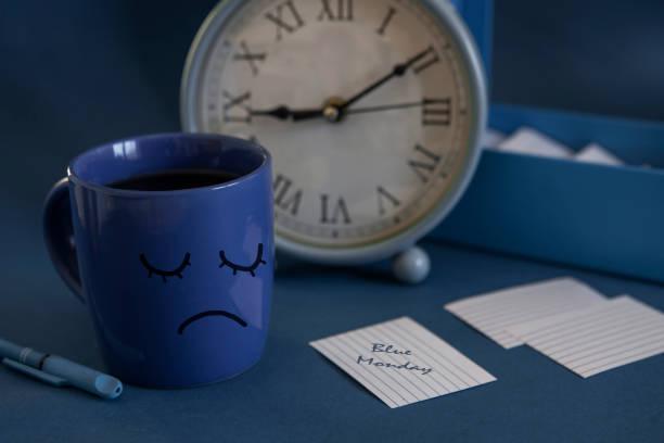 l'inizio della giornata lavorativa il lunedì blu. tazza di tè, sveglia e una nota con il testo blue monday. il giorno più depresso dell'anno - blue monday foto e immagini stock