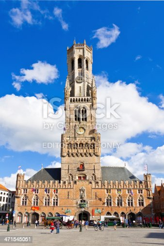 Bruges, Belgium - June 22, 2012: The Belfry (Belltower) in Market Square (Markt) in historic city center. It is a medieval bell tower that  formerly housed a treasury and the municipal archives, and served as an observation post for spotting fires and other danger. In the 16th century the tower received a carillon, allowing the bells to be played by means of a hand keyboard. Bruges has most of its medieval architecture intact and has been a UNESCO World Heritage Site since 2000. Tourists are walking around.