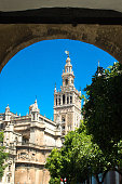 The Bell tower of the Seville Cathedral viewed through nearby arch through a wall.