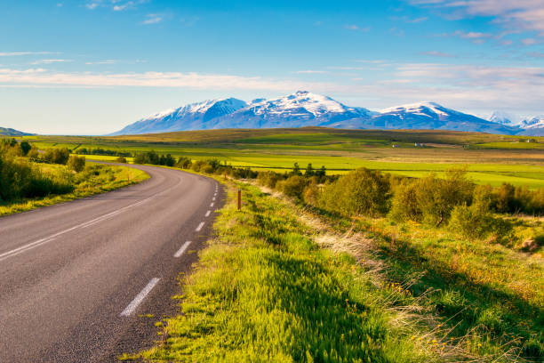 the bend of the asphalt road among green meadows in front of the snowcapped mountain peaks on Iceland stock photo