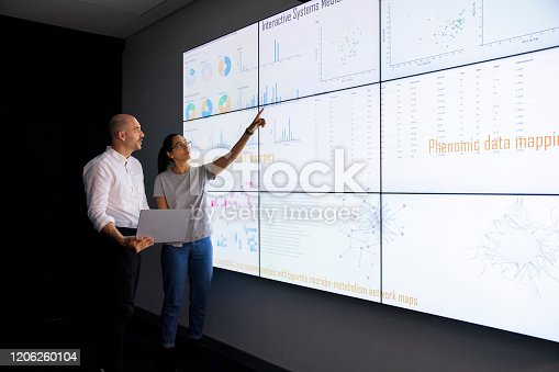 Discussion in front of a large information device about universal detection of genes in a specific biological sample.