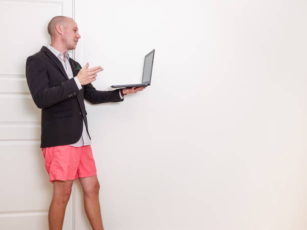The benefits of video conference / videotelephony. The benefits of video conference / videotelephony. Man wearing suit jacket and orange shorts, holding a laptop computer. shorts stock pictures, royalty-free photos & images