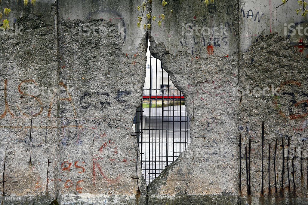 The Berlin Wall with a gap that's filled with iron bars stock photo