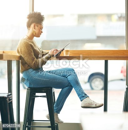 Shot of an attractive young woman using a digital tablet in a cafe