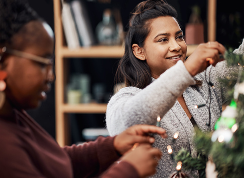 Shot of two young women decorating a Christmas tree at home