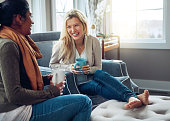 Shot of two young women having coffee together on a relaxing day at home