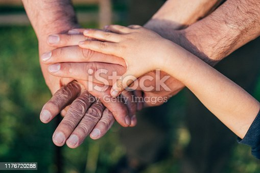 Close-up of group of people with stacking hands.