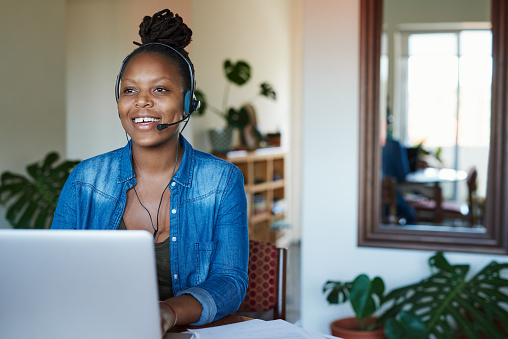 Shot of a young woman using a laptop and headset while working from home