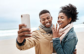 Cropped shot of a young couple taking a selfie at the beach
