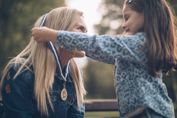 The best mummy Daughter giving a mother a gold medal in public park medal stock pictures, royalty-free photos & images
