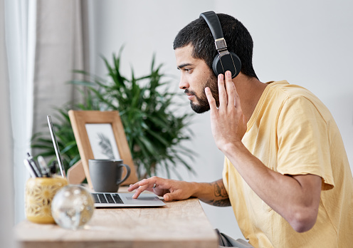 Shot of a young man using a laptop and headphones while working from home