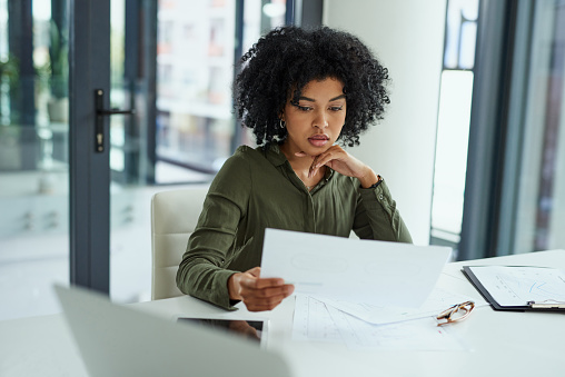 Shot of a young businesswoman going over paperwork in a modern office