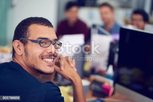 Shot of a smiling young designer sitting at his computer with colleagues in the background