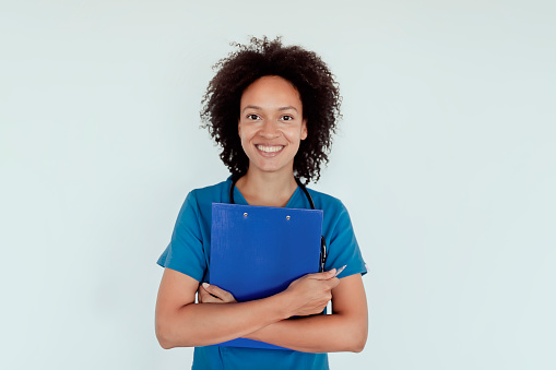 Mixed Race Female Nurse or Female Doctor in Uniform Standing while Holding a Clipboard Isolated on Gray Background