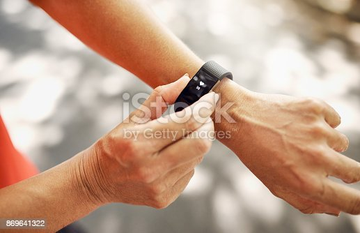 Shot of an unrecognizable woman checking her fitness tracker after a run