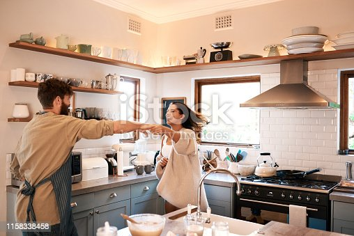 Shot of a happy young couple dancing in the kitchen while preparing breakfast at home