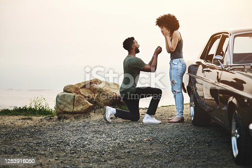 Shot of a young man proposing to his girlfriend during a road trip