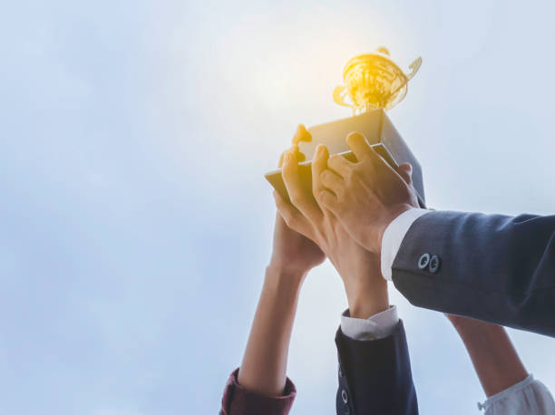 The best team helped each other reach their goals target to success. The hand of a business man and business women pick up the trophy and celebrate together. Teamwork of successful concept The best team helped each other reach their goals target to success. The hand of a business man and business women pick up the trophy and celebrate together. Teamwork of successful concept achievement stock pictures, royalty-free photos & images