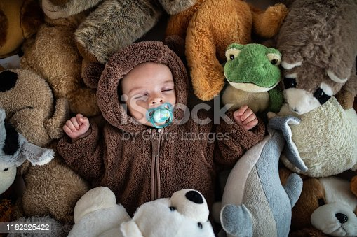 Sleeping little baby in warm baby clothing taking a nap between heap of soft toys