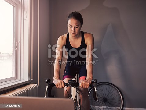 Cropped shot of a young woman working out on an exercise bike at home