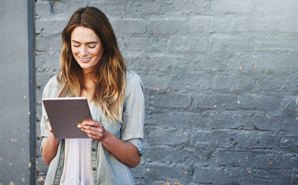 The best way to keep up with social media Shot of a young woman standing outdoors and using a digital tablet against a gray wall touchpad stock pictures, royalty-free photos & images