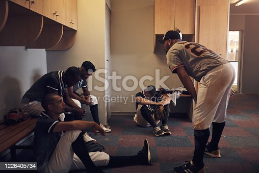 Shot of a young man yelling at his fellow baseball players in a locker room