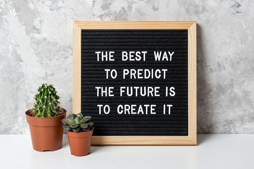 The best way to predict the future is to create it. Motivational quote on letter board, cactus, succulent flower on white table. Concept inspirational quote of the day. Front view.