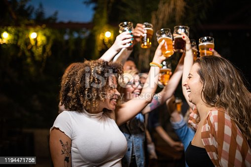 Cheerful group of multi-ethnic people having fun at party while everybody dancing and drinking beer at open night club