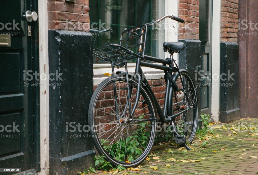 The bicycle is parked next to the house in Amsterdam in Europe. European style of life. A popular, healthy and eco-friendly means of transportation in Holland. stock photo