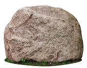 The big ancient mossy granite stone lie on a forest green grass glade.