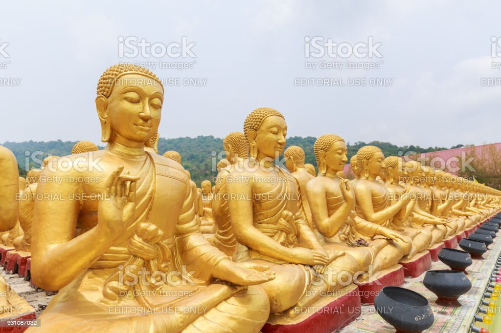 The big golden Buddha statue among many small Buddha statues in countryside public temple named MAKHA BUCHA BUDDHIST MEMORIAL PARK in Nakornnayouk, Thailand. stock photo