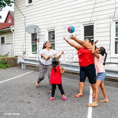 The big happy Latino, Mexican-American family - the mother, body-positive cheerful woman, and kids, girls of different ages - playing with a ball outdoor in the sunny hot summer day at the parking lot nearby his house in Pennsylvania, USA