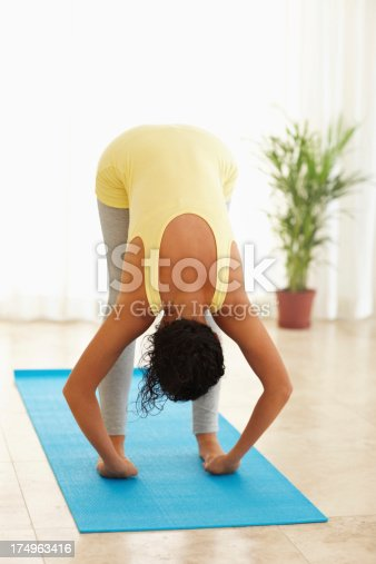 An attractive young woman doing the big toe pose during yoga
