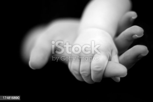 Baby boy holding his mother's hand.Black and white photo.