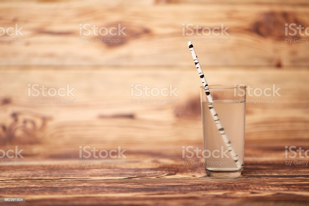 the birch juice on wooden background with straw foto