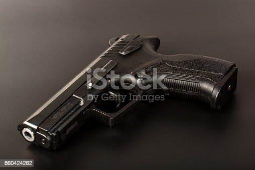 istock The black gun (pistol) on a dark background close up. Isolate. 860424262