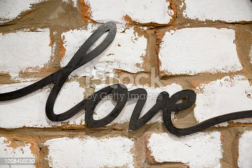 The black metal word Love is hanging against a brick wall background in Cafe. White bricks with brown seams background.