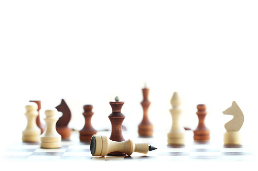 selective focus of chess wooden pieces on white background, black queen defeats white king, concept of success and goal achievement