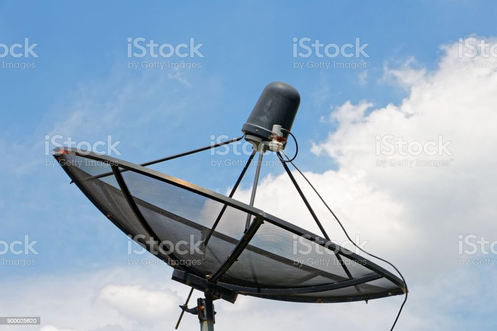 The black satellite dish on the roof on a white cloud background and blue sky, Meaning of Communication and Technology. stock photo