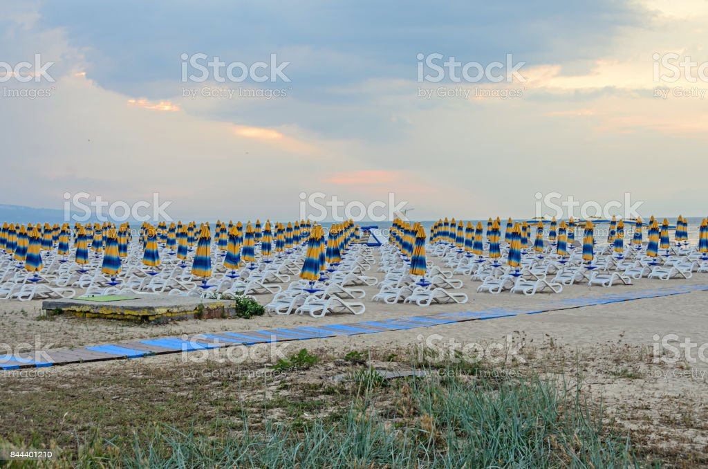 The Black Sea shore from Albena, Bulgaria with golden sands, blue fresh water, sunbeds and umbrellas at sunset stock photo