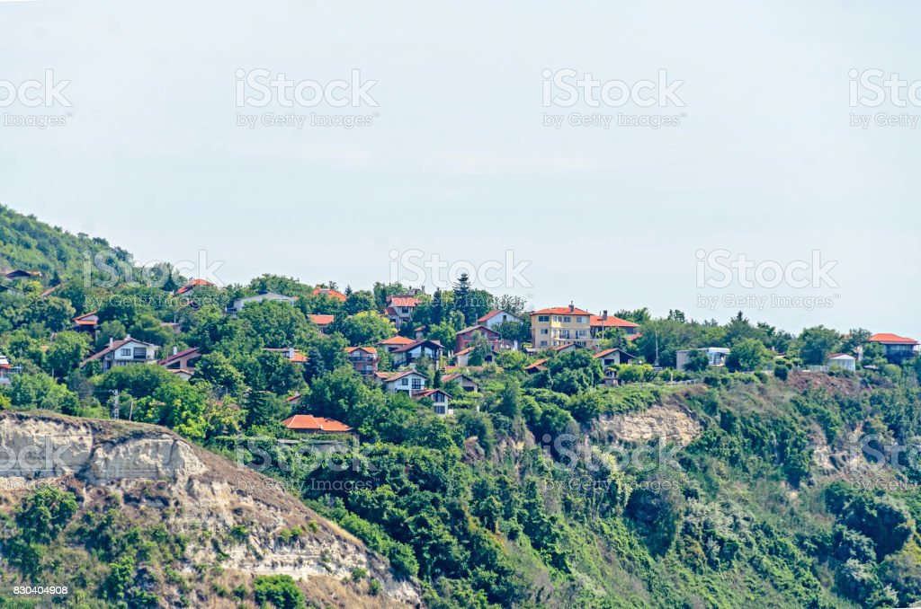 The Black Sea shore, green hills with houses, blue clouds sky. City Balchik coast, blue sea water stock photo