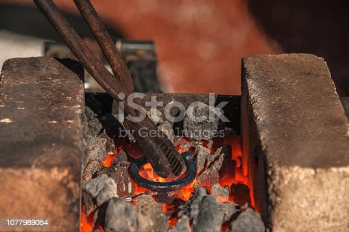 istock The blacksmith holds the tongs and heats the iron billet while the iron hotly creates a horseshoe on the anvil 1077989054
