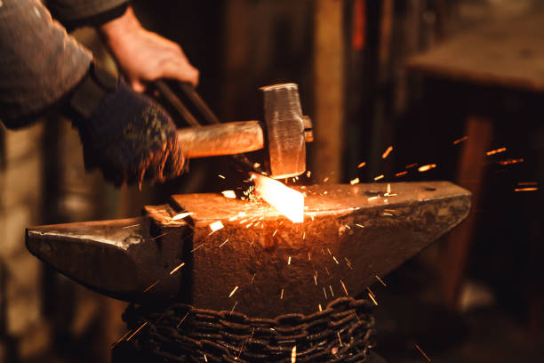The blacksmith manually forging the red-hot metal on the anvil in smithy with spark fireworks. The blacksmith manually forging the red-hot metal on the anvil in smithy with spark fireworks anvil stock pictures, royalty-free photos & images