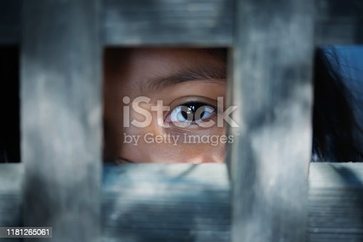 The blank stare of a child's eye who is standing behind what appears to be a wooden frame