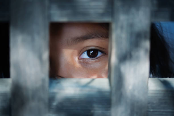 the blank stare of a child's eye who is standing behind what appears to be a wooden frame - victim stock pictures, royalty-free photos & images