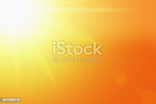 Blazing sun radiating solar energy on a background of gold deepening to orange, with radiating rays and lens flare. Ample copy space or could be used as nature background..