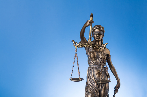 The blindfold goddess of justice Themis or Justitia on blue background