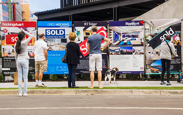 The Block - Blocktagon Melbourne, Australia - November 28, 2015: Visitors reading a row of estate agent signs outside a newly-renovated apartment building at 5 Commercial Rd, South Yarra. Formerly a derelict hotel, the site was the focus of Series 11 of popular Channel Nine TV series The Block. a reality renovation contest. real estate sign stock pictures, royalty-free photos & images