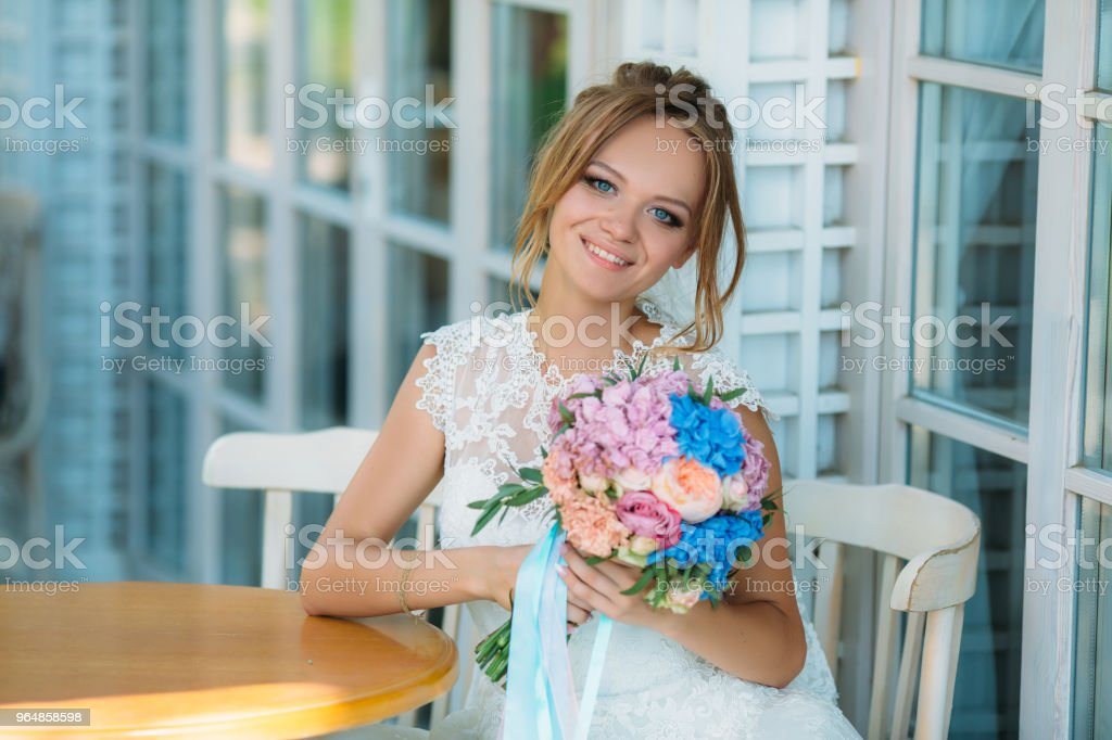 The blond bride with bright blue eyes is smiling broadly. A girl with a flower bouquet is happy to marry a loved one royalty-free stock photo