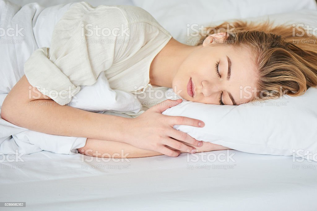 The blonde girl is sleeping on white bed - Royalty-free Adult Stock Photo